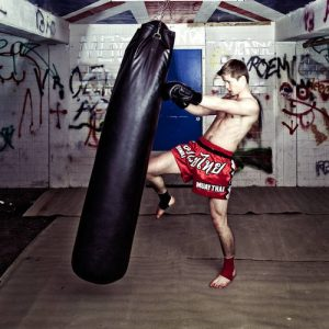 Athletic muay thai boxer giving a forceful knee kick during a training with a boxing bag