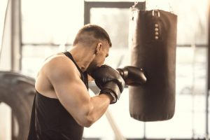 man punching a heavy bag with gloves