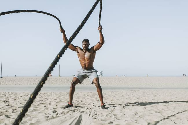 Fit man on beach doing rope exercises.