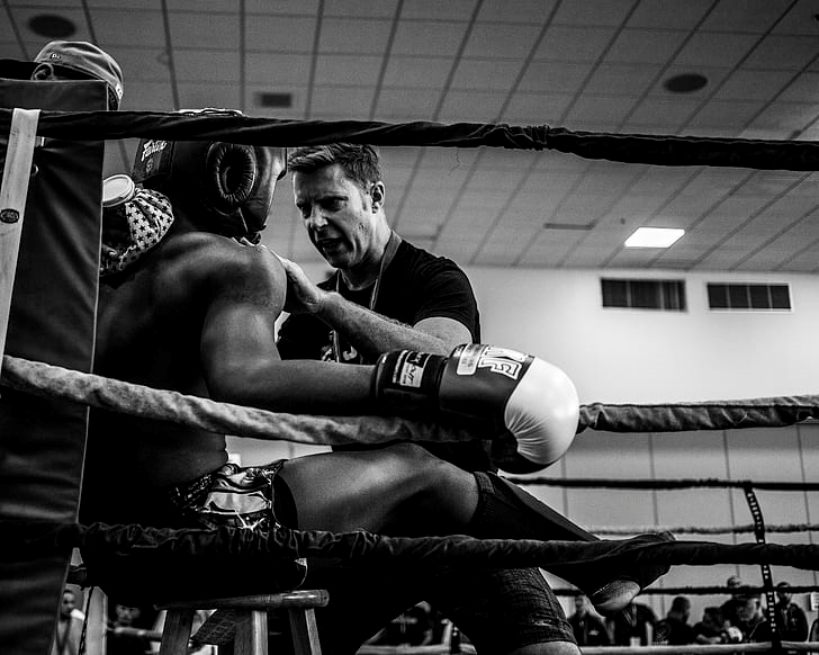 A fighter receives instructions from his coach during a sparring session.