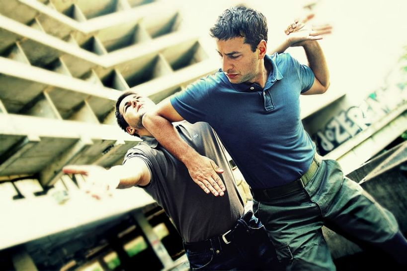 One man uses his elbow to stun his assailant in a self-defense scenario.